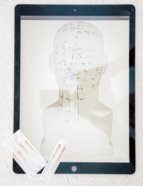 Tablet mit Bild eines gezeichneten Kopfes als Umriss mit den Meridianen und Akupunkturpunkten