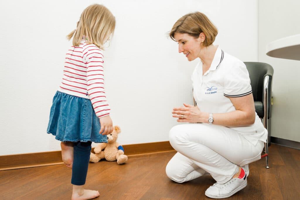 Mädchen steht auf einem Bein vor Frau Dr. Doepfer