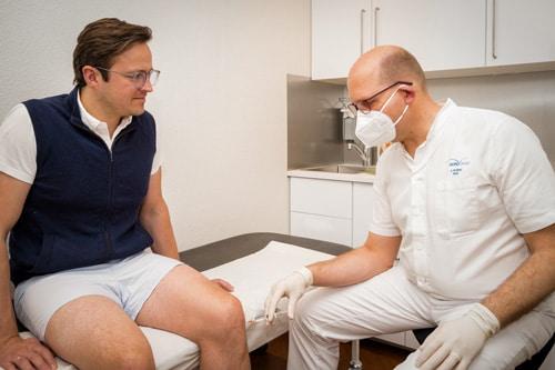 Dr. Knöbel injiziert das Knorpelschutzpräparat ins Knie des vor ihm sitzenden Patienten