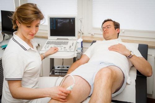 Frau Dr. Doepfer führt eine Sonografie durch am Knie eines liegenden Patienten