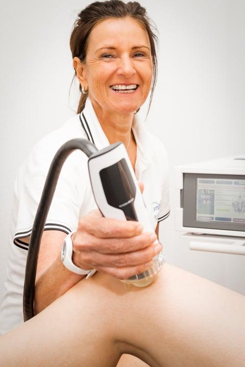 Frau Dr. Thon behandelt das Knie eines Patienten mit Stoßwellentherapie