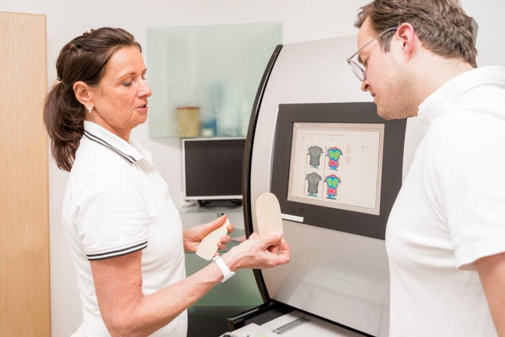 Frau Dr. Thon zeigt einem Patienten seine Fersenkissen und erläutert das Ergebnis der Vermessung seiner Wirbelsäule.