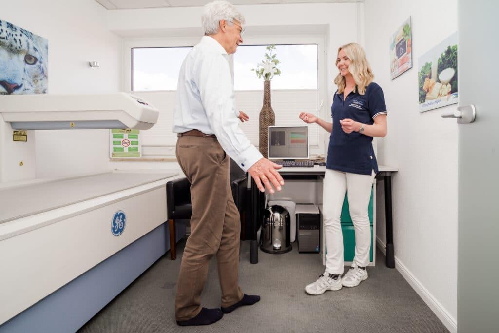 Medizinische Fachangestellte ermittelt beim Patienten das Sturzrisikos durch Gleichgewichtstest im Tandemstand