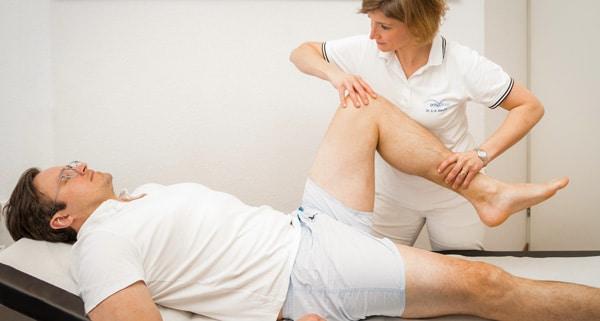 Frau Dr. Doepfer prüft die Beweglichkeit des linken Beines des liegenden Patienten