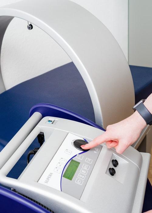 Zeigefinger einer Hand am Gerät, mit dem die pulsierende Magnetfeldtherapie durchgeführt werden kann